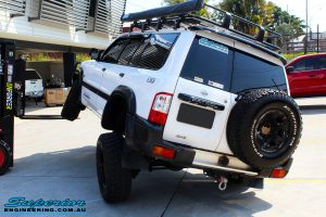 """Rear left side view of a White Nissan GU Patrol outside flexing its front left wheel after fitment of a Superior Remote Reservoir Hyperflex 4"""" Inch Lift Kit"""