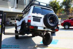 """Rear left view of a White Nissan GU Patrol flexing its rear left wheel after fitment of a Superior Remote Reservoir Hyperflex 4"""" Inch Lift Kit"""