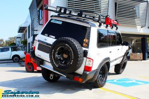 """Rear right side view of a White Nissan GU Patrol flexing after fitment of a Superior Remote Reservoir Hyperflex 4"""" Inch Lift Kit"""