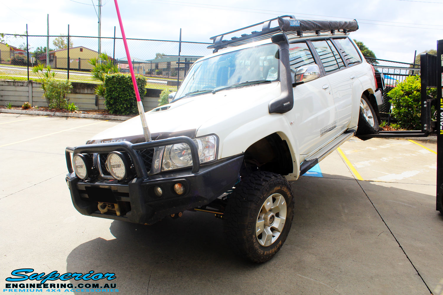 """Front left side view of a flexed White Nissan GU Patrol Wagon after fitment of a Superior Nitro Gas 2"""" Inch Lift Kit, Coil Tower Brace Kit, Superior Hybrid Superflex Radius Arms, Airbag Man Coil Air Kit and Superior Adjustable Hollow Bar Drag Link"""