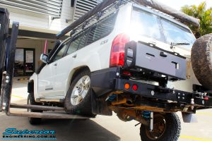 """Rear left side view of a White Nissan GU Patrol Wagon flexed up after fitment of a Superior Nitro Gas 2"""" Inch Lift Kit, Coil Tower Brace Kit, Superior Hybrid Superflex Radius Arms, Airbag Man Coil Air Kit and Superior Adjustable Hollow Bar Drag Link"""