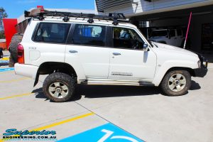 """Right side view of a flexed White Nissan GU Patrol Wagon before fitment of a Superior Nitro Gas 2"""" Inch Lift Kit, Coil Tower Brace Kit, Superior Hybrid Superflex Radius Arms, Airbag Man Coil Air Kit and Superior Adjustable Hollow Bar Drag Link"""