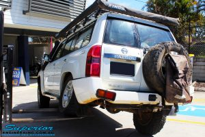 """Rear left side view of a White Nissan GU Patrol Wagon flexed up before fitment of a Superior Nitro Gas 2"""" Inch Lift Kit, Coil Tower Brace Kit, Superior Hybrid Superflex Radius Arms, Airbag Man Coil Air Kit and Superior Adjustable Hollow Bar Drag Link"""