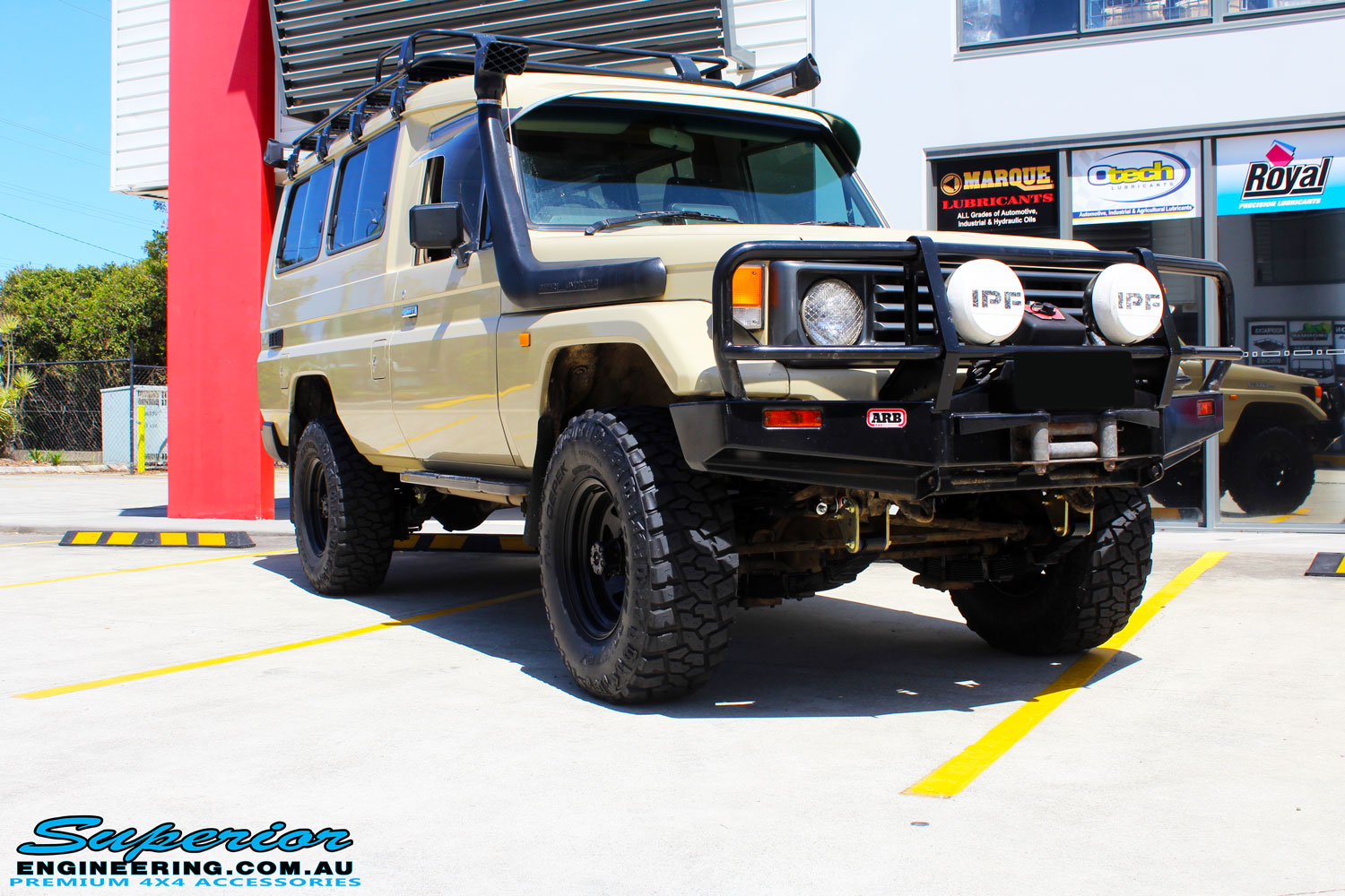 """Right front side view of a Beige Toyota 75 Series Landcruiser Troopcarrier after fitment of a EFS 2"""" Inch Lift Kit"""