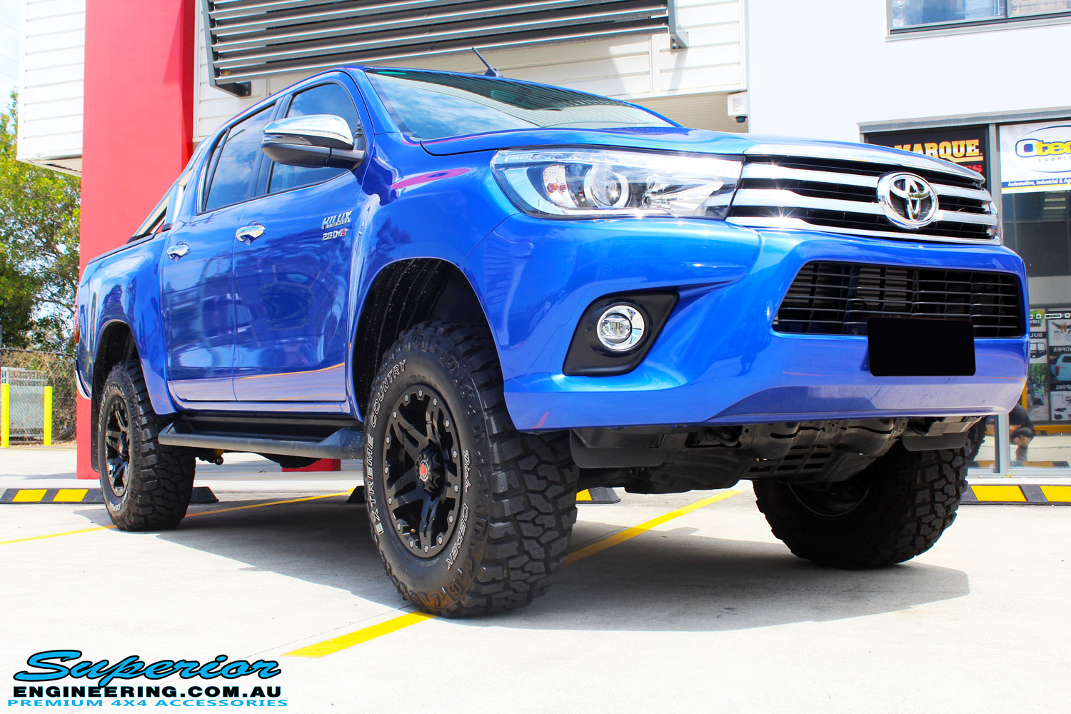 """Right front side view of a Toyota Revo Hilux Dual Cab in Blue after fitment of a 3"""" Inch Lift Kit with Superior Upper Control Arms and Diff Drop Kit"""