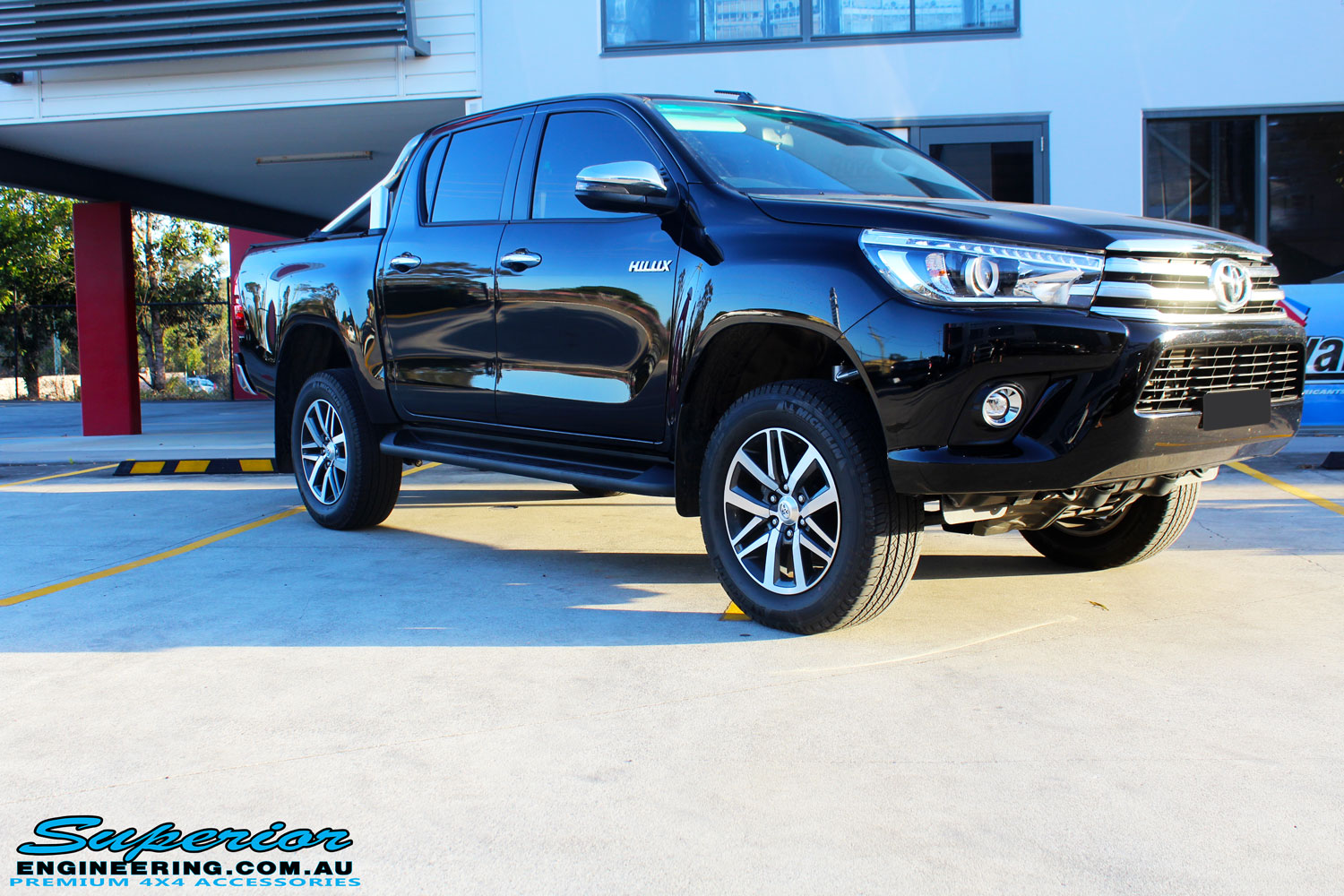 """Right side view of a Toyota Revo Hilux Dual Cab in Black after fitment of a Superior Remote Reservoir 3"""" Inch Lift Kit"""