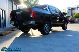 "Rear right view of a Toyota Revo Hilux Dual Cab in Black after fitment of a Superior Remote Reservoir 3"" Inch Lift Kit"