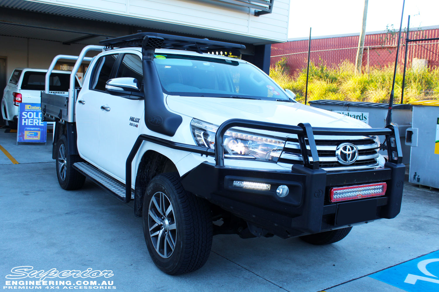 "Left front side view of a White Toyota Revo Hilux after fitting a Superior Remote Reservoir 2"" Inch Lift Kit"