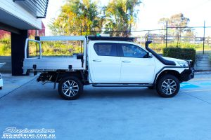 """Left side view of a White Toyota Revo Hilux after fitting a Superior Remote Reservoir 2"""" Inch Lift Kit"""