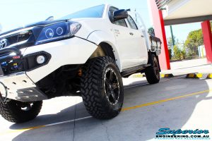 """Front left close up shot of a Toyota Vigo Hilux Dual Cab in White after fitment of a Superior Nitro Gas 2"""" Inch Lift Kit, Rhino 4x4 Evolution 3D Winch Bar, VRS Winch, Legendex 409 Stainless Steel 3"""" Exhaust, Legendex Thrust Monkey Throttle Control, Legendex Rock Sliders, Legendex Optimizer Remap Service, Stainless Snorkel & Nitto Trail Grappler Tyres"""