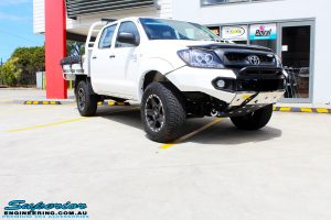 "Right front side view of a Toyota Vigo Hilux Dual Cab in White after fitment of a Superior Nitro Gas 2"" Inch Lift Kit, Rhino 4x4 Evolution 3D Winch Bar, VRS Winch, Legendex 409 Stainless Steel 3"" Exhaust, Legendex Thrust Monkey Throttle Control, Legendex Rock Sliders, Legendex Optimizer Remap Service, Stainless Snorkel & Nitto Trail Grappler Tyres"