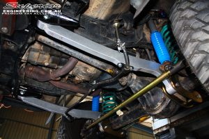 """Right side underbody close up shot looking up on the fitted Superior 4340m Tie Rod Bar, Coil Springs, Adjustable 3"""" Remote Reservoir Shocks & Hyperflex Radius Arms with Drop Boxes"""