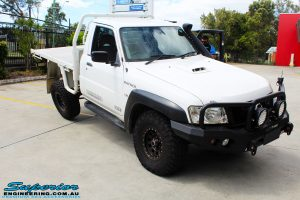 """Front right side view of a White Nissan GU Patrol Ute showing its rear flex after fitting the Superior 4"""" Inch Remote Reservoir Hyperflex Kit"""