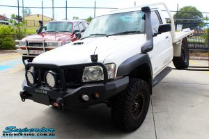 """Front left side view of a White Nissan GU Patrol Ute showing its front flex after fitting the Superior 4"""" Inch Remote Reservoir Hyperflex Kit"""