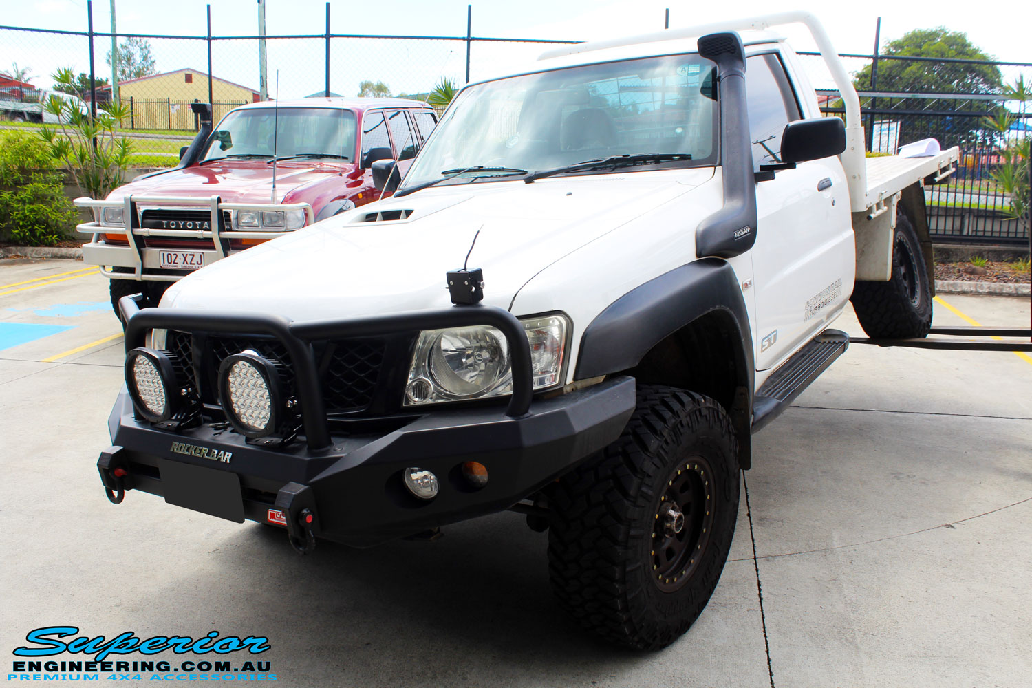 "Front left side view of a White Nissan GU Patrol Ute showing its front flex after fitting the Superior 4"" Inch Remote Reservoir Hyperflex Kit"