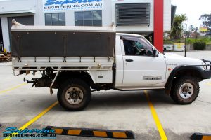 Right side view of a Nissan GU Patrol Ute in Gold On The Hoist @ Superior Engineering Deception Bay Showroom