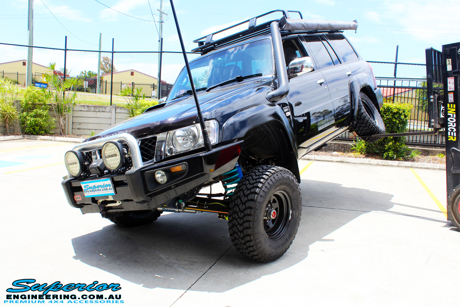 "Front left side view of a Black Nissan GU Patrol Wagon being flexed after fitting the Superior 2"" Inch Remote Reservoir Hyperflex Kit with Front & Rear Superflex Sway Bar Kits, Comp Spec 4340m Tie Rod, Long Arms and Coil Tower Brace Kit"
