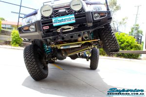 """Front on underbody shot of a Black Nissan GU Patrol Wagon being flexed after fitting the Superior 2"""" Inch Remote Reservoir Hyperflex Kit with Front & Rear Superflex Sway Bar Kits, Comp Spec 4340m Tie Rod, Long Arms and Coil Tower Brace Kit"""