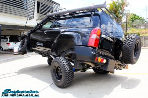 "Rear left side view of a Black Nissan GU Patrol Wagon being flexed after fitting the Superior 2"" Inch Remote Reservoir Hyperflex Kit with Front & Rear Superflex Sway Bar Kits, Comp Spec 4340m Tie Rod, Long Arms and Coil Tower Brace Kit"