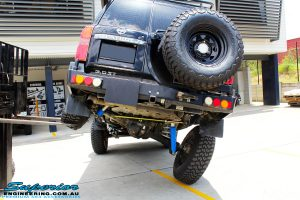 """Mid rear view of a Black Nissan GU Patrol Wagon being flexed after fitting the Superior 2"""" Inch Remote Reservoir Hyperflex Kit with Front & Rear Superflex Sway Bar Kits, Comp Spec 4340m Tie Rod, Long Arms and Coil Tower Brace Kit"""