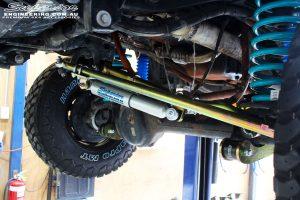 Front left view of a Superior Adjustable Panhard Rod, 4340m Solid Draglink and Steering Damper