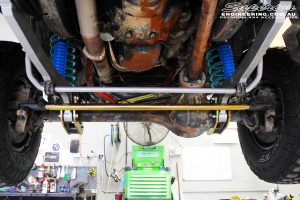 Mid underbody view looking forward of the fitted Comp Spec 4340m Tie Rod, Superflex Sway Bar Kit & Hyperflex Radius Arms