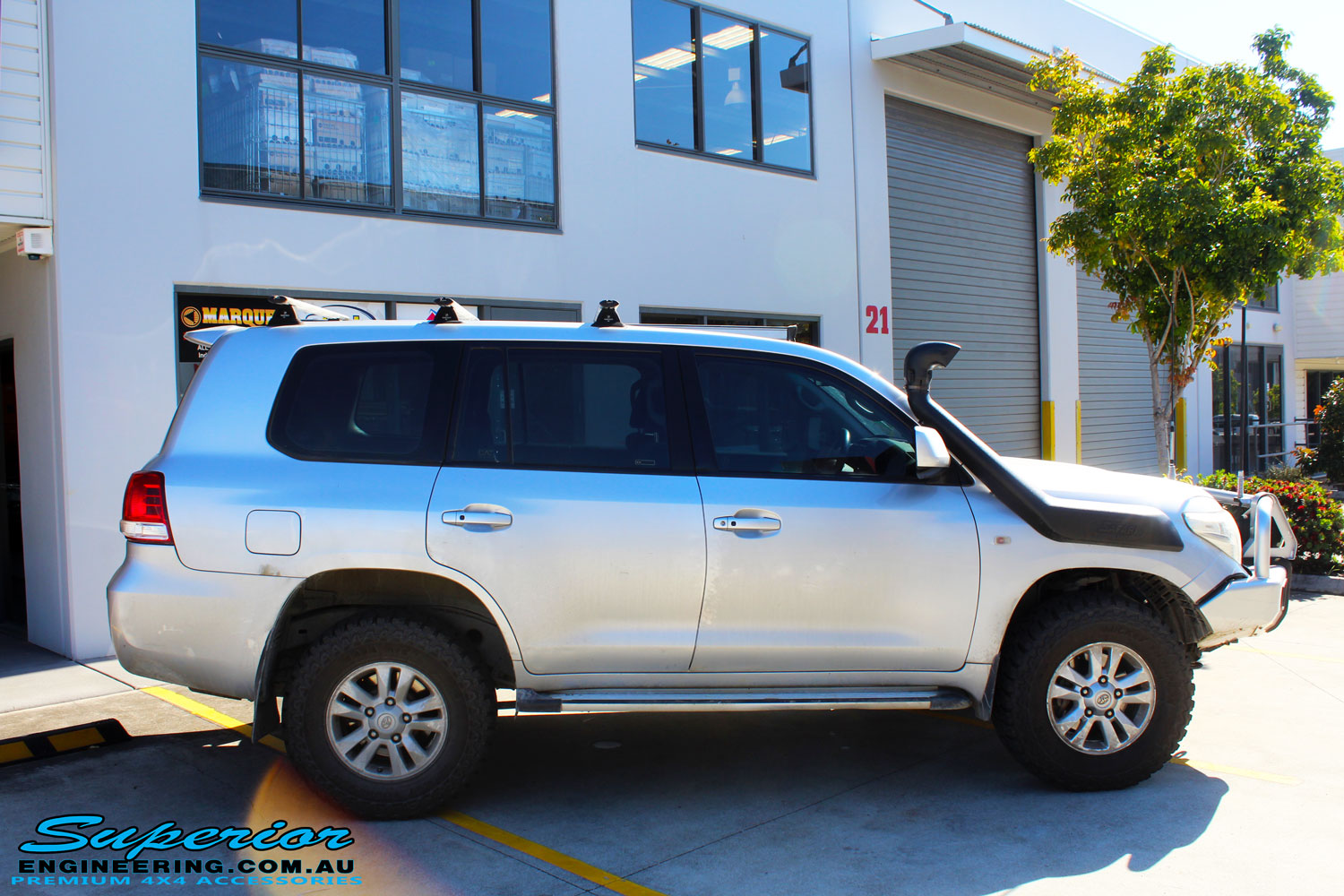 """Right side view of a Silver Toyota 200 Series Landcruiser after fitment of a Superior Remote Reservoir 2"""" Inch Lift Kit"""