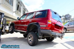 """Rear left view of a Toyota 80 Series Landcruiser in Maroon showing its rear flex after fitment of a Superior Remote Reservoir Hyperflex 3"""" Inch Lift Kit"""