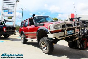 """Front right side view of a Toyota 80 Series Landcruiser in Maroon showing its flex after fitment of a Superior Remote Reservoir Hyperflex 3"""" Inch Lift Kit"""