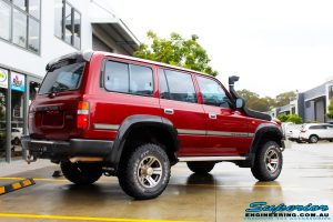 """Rear right view of a Toyota 80 Series Landcruiser in Maroon before fitment of a Superior Remote Reservoir Hyperflex 3"""" Inch Lift Kit"""
