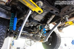 Mid left underbody shot looking forward on the fitted Hyperflex Radius Arms, Adjustable Monotube Remote Reservoir Shocks + Coil Springs