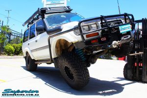 """Left front view of a Toyota 80 Series Landcruiser in White showing its flex after fitment of a Superior Remote Reservoir Superflex 3"""" Inch Lift Kit with a Superior Comp Spec Draglink & Superior Comp Spec Tie Rod"""