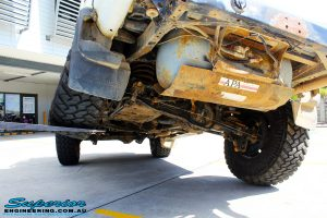 """Rear left underbody shot of a Toyota 80 Series Landcruiser in White showing its flex before fitment of a Superior Remote Reservoir Superflex 3"""" Inch Lift Kit with a Superior Comp Spec Draglink & Superior Comp Spec Tie Rod"""