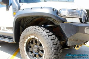 Close up front right wheel arch view of a White Toyota FJ Cruiser after fitment of Superior Chromoly Upper Control Arms