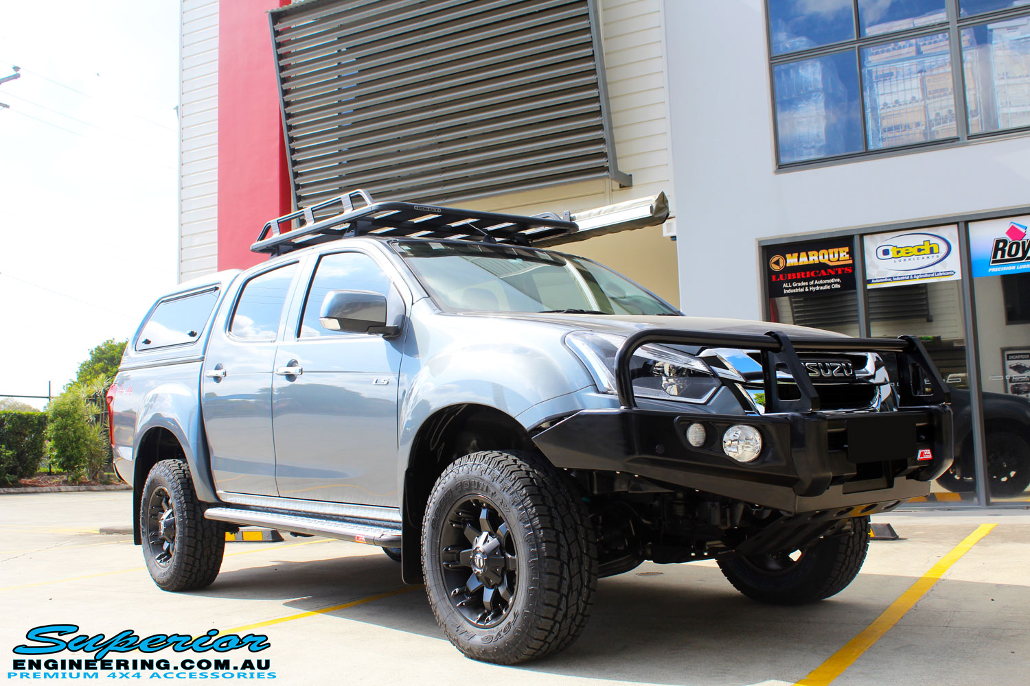 "Right front side view of a Grey Isuzu D-Max Dual Cab after fitment of a Superior Nitro Gas 2"" Inch Lift Kit, MCC Drawer System, MCC 4x4 Bullbar, Hayman Reece Towbar, MCC 4x4 Side Steps, EGR Premium Canopy, Rhino Roof Rack & a Ironman 4x4 Instant Awning with LED's"