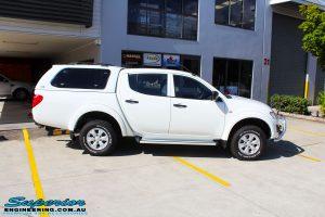 "Right side view of a Mitsubishi MN Triton in White before fitment of a Superior Nitro Gas 2"" Inch Lift Kit"