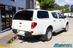 """Rear right view of a Mitsubishi MN Triton in White before fitment of a Superior Nitro Gas 2"""" Inch Lift Kit"""