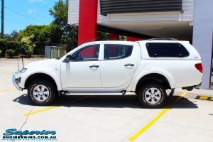"Left side view of a Mitsubishi MN Triton in White after fitment of a Superior Nitro Gas 2"" Inch Lift Kit"