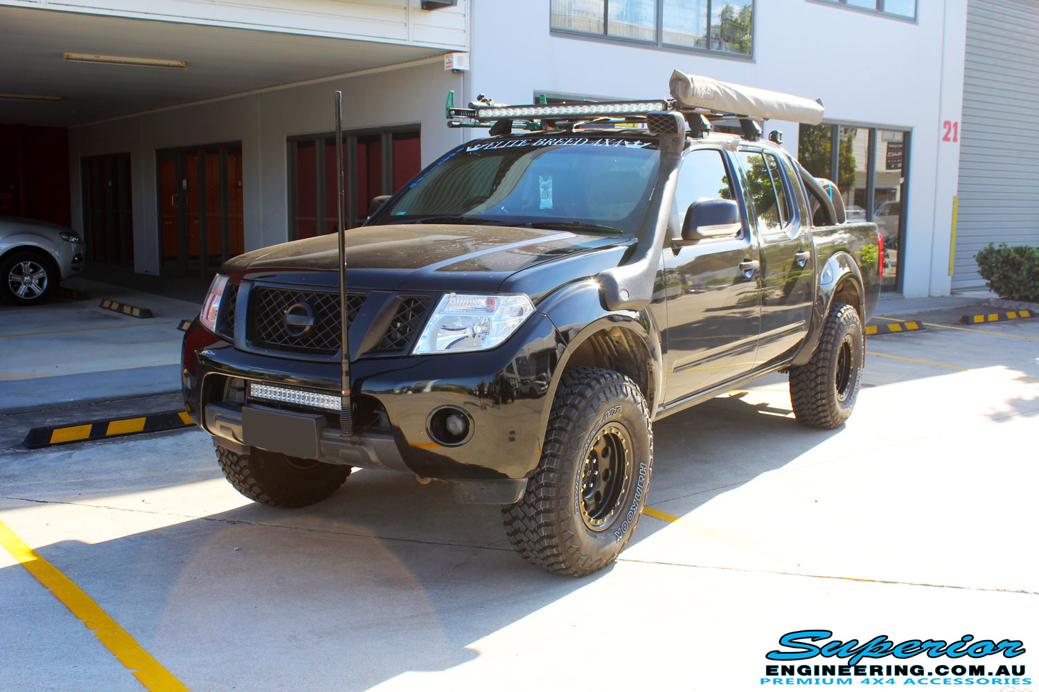 "Right left side view of a Black Nissan D40 Navara Dual Cab after fitment of a Superior Nitro Gas 2"" Inch Lift Kit + Upper Control Arms"