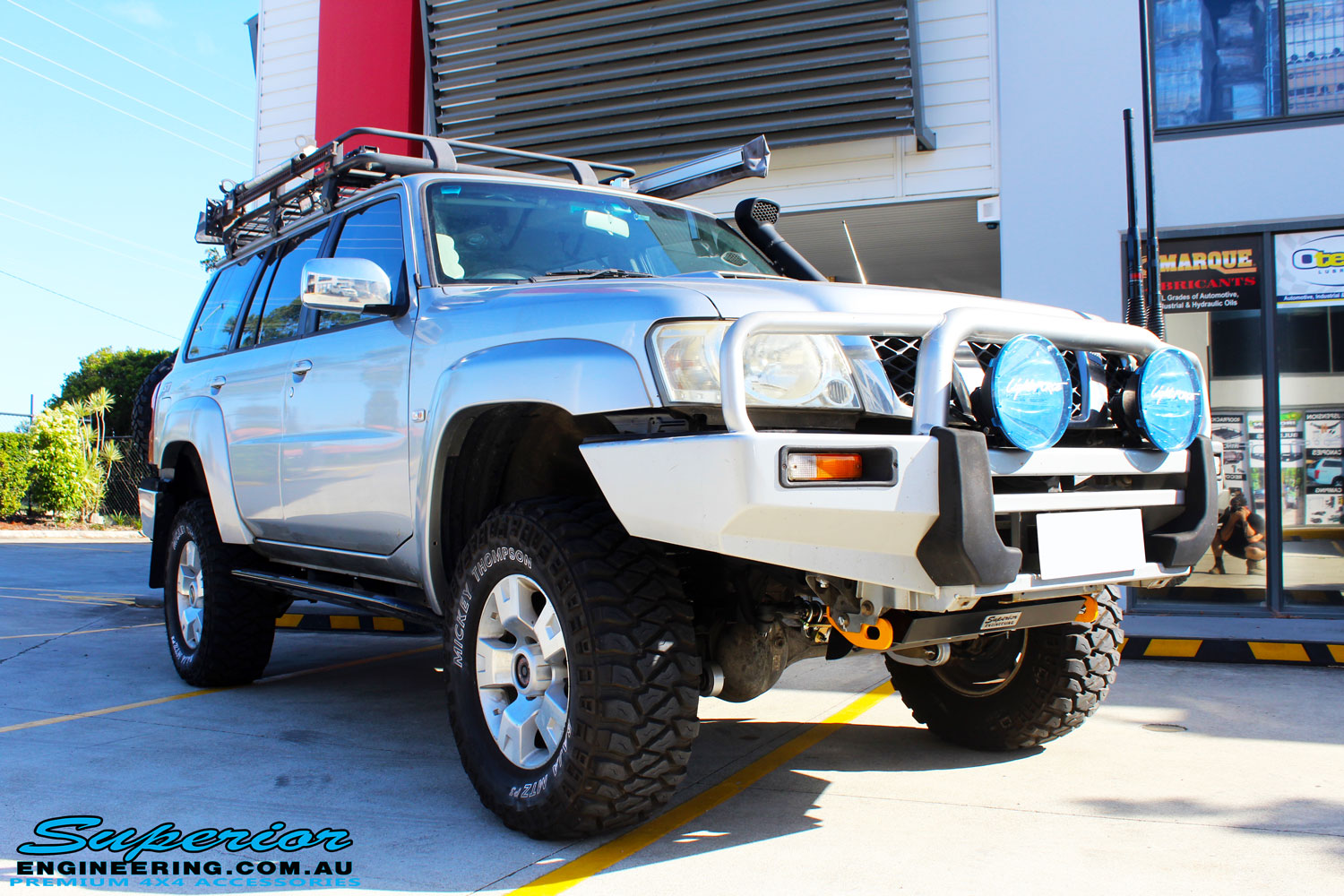 "Right front side view of a Silver Nissan Patrol GU Wagon after fitting a Superior Remote Reservoir Hybrid Dropped Radius 3"" Inch Lift Kit with Hybrid Radius Arms, Steering Damper, Upper & Lower Control Arms, Comp Spec Draglink, Front & Rear Panhard Rods, Superior Coil Tower Brace Kit, Superior Front Steering Radiator Guard, Body Lift and Airbag Man Coil Helper Ait Kit"
