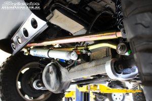 Front left underbody shot of the fitted Superior Steering Damper, Comp Spec Draglink and Adjustable Panhard Rod