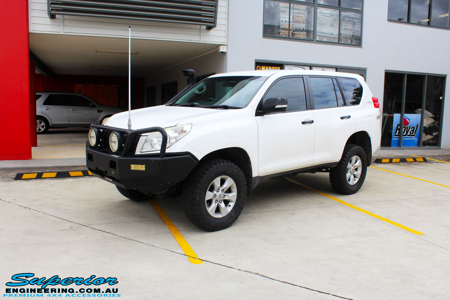 """Right front side view of a White Toyota 150 Landcruiser Prado Wagon after fitment of a Superior Remote Reservoir 2"""" Inch Lift Kit with King Coil Springs and a Ironman 4x4 Snorkel"""