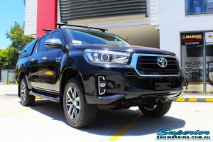 """Right front side view of a Toyota Revo Hilux Dual Cab in Black before fitment of a Fox 2.0 Performance Series IFP 2"""" Inch Lift Kit + Upper Control Arms"""