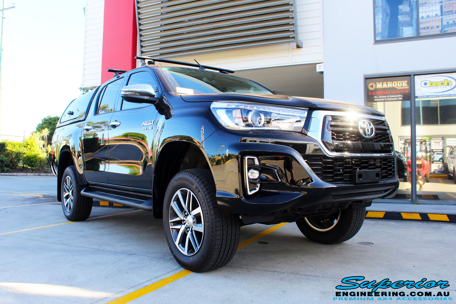 "Right front side view of a Toyota Revo Hilux Dual Cab in Black after fitment of a Fox 2.0 Performance Series IFP 2"" Inch Lift Kit + Upper Control Arms"