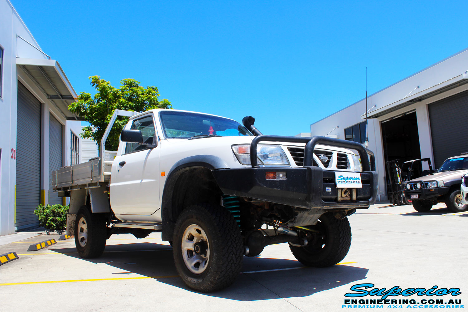 "Right front side view of a White Nissan GU Patrol Ute Wagon after fitment of a Fox 2.0 Performance Series IFP Hybrid Dropped Radius 5"" Lift Kit with Superior Sway Bar Extensions"