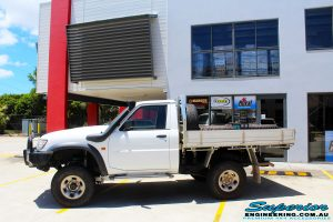 """Left side view of a White Nissan GU Patrol Ute Wagon after fitment of a Fox 2.0 Performance Series IFP Hybrid Dropped Radius 5"""" Lift Kit with Superior Sway Bar Extensions"""