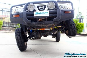 Front mid underbody view of this Nissan GU Patrol Ute being flexed from the front left tyre after fitment of a Superior 4-5 Inch Lift Kit with Superior Remote Reservoir Shocks & Superior Hybrid 5 Link Radius Arms