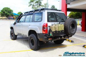 Rear left view of a Nissan GU Patrol Wagon in Silver On The Hoist @ Superior Engineering Deception Bay Showroom getting fitted with a Superior Coil Tower Brace Kit