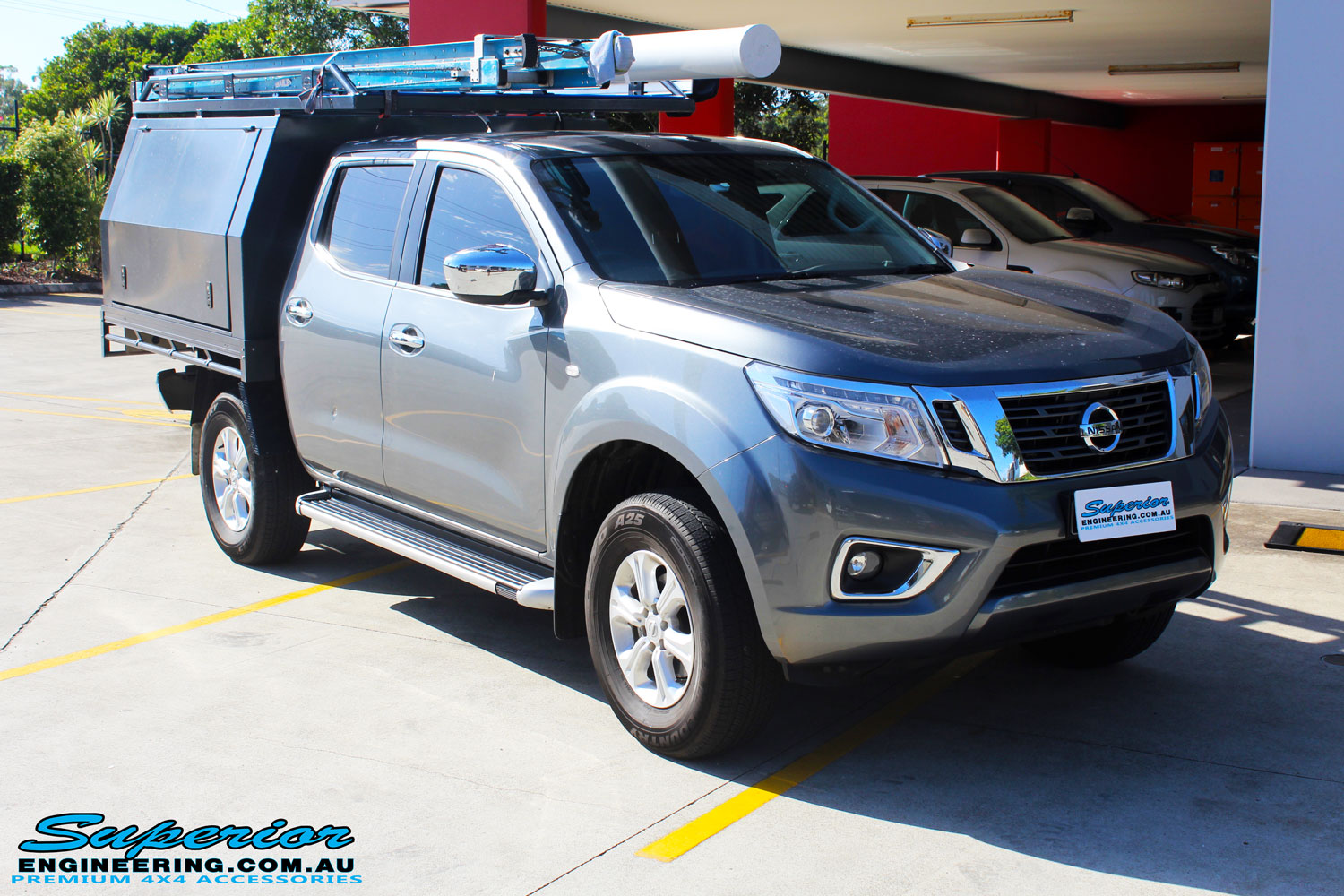 Right front side view of a Nissan NP300 Navara in White On The Hoist @ Superior being fitted with a Chassis Brace/Repair Plate