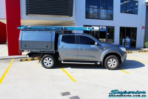 Right side view of a Nissan NP300 Navara in White On The Hoist @ Superior being fitted with a Chassis Brace/Repair Plate